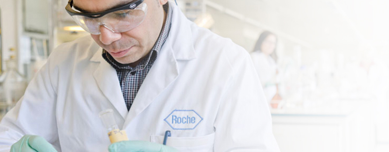 Male scientist wearing Roche lab coat and protective glasses working in a lab