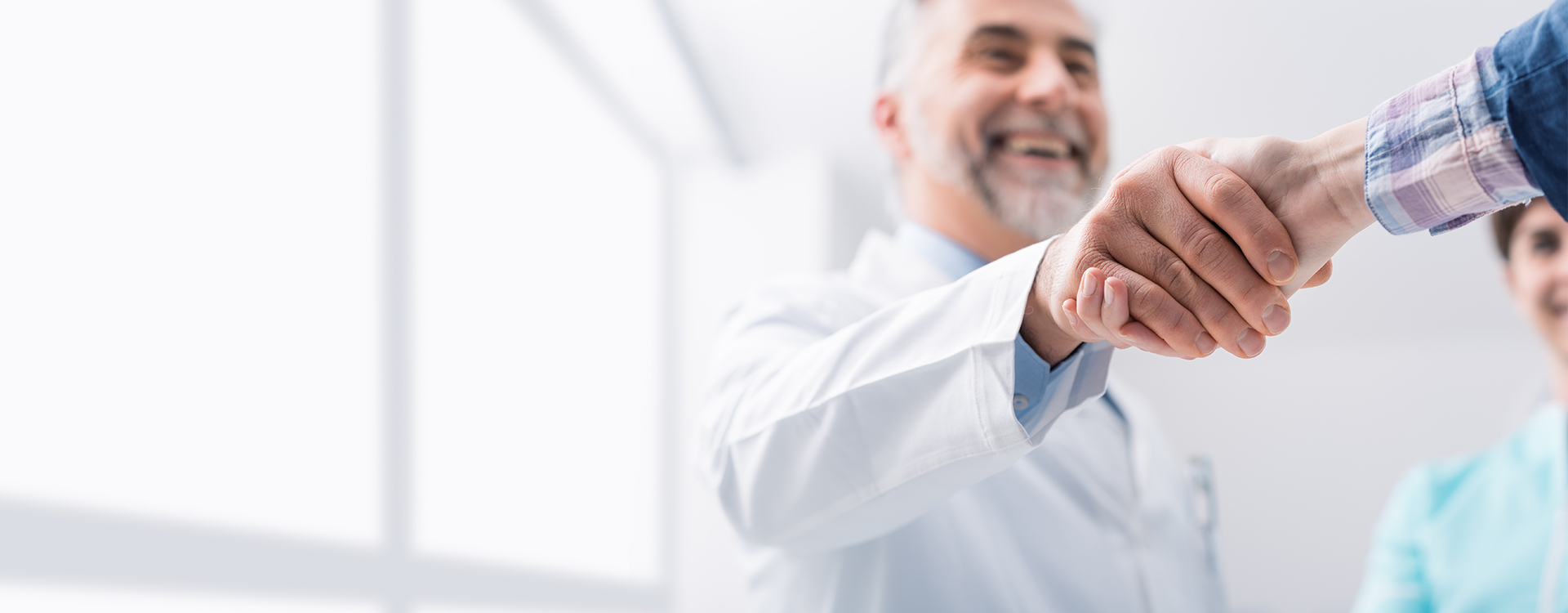 Older male in white lab coat shaking hands with a businessman