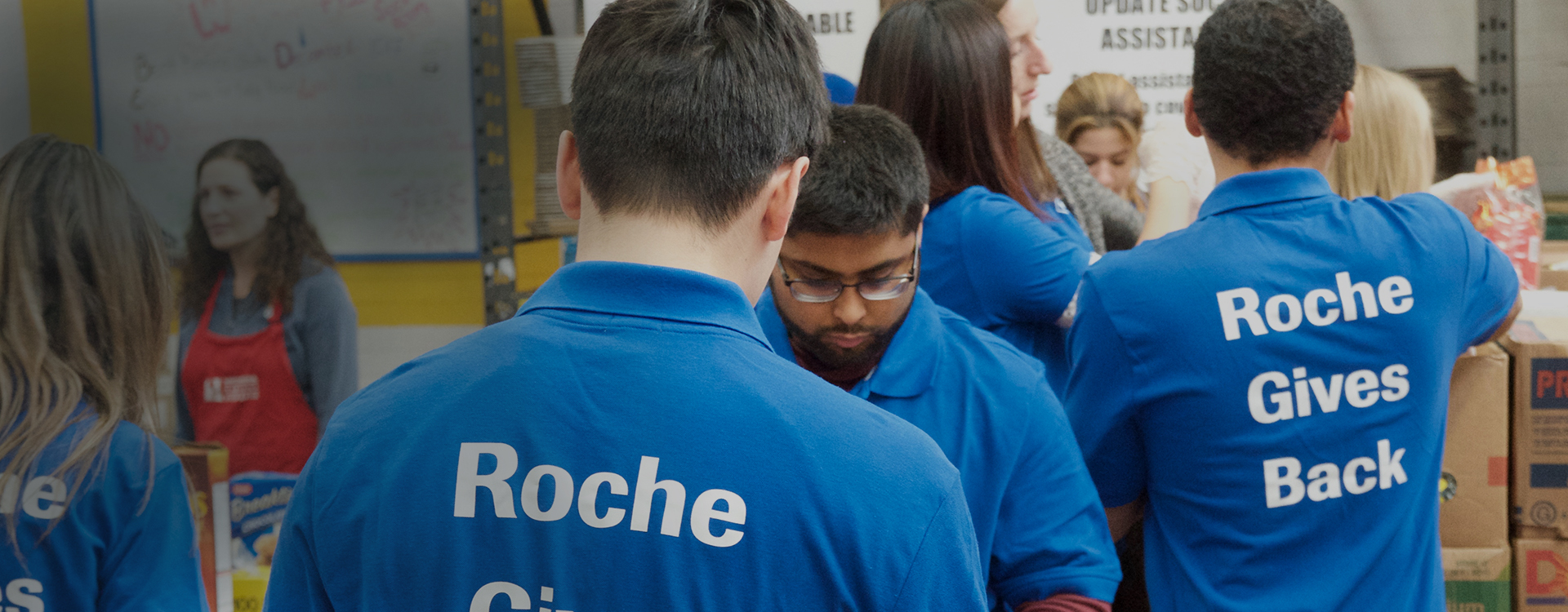 Group of employees working at a food bank wearing Roche Gives Back shirts